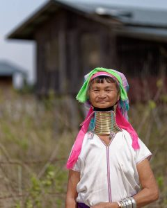 Karen long neck tribe woman in front of traditional house