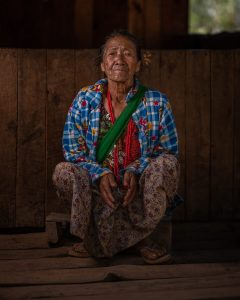 sitting Chin tribe woman with face tattoos, Myanmar