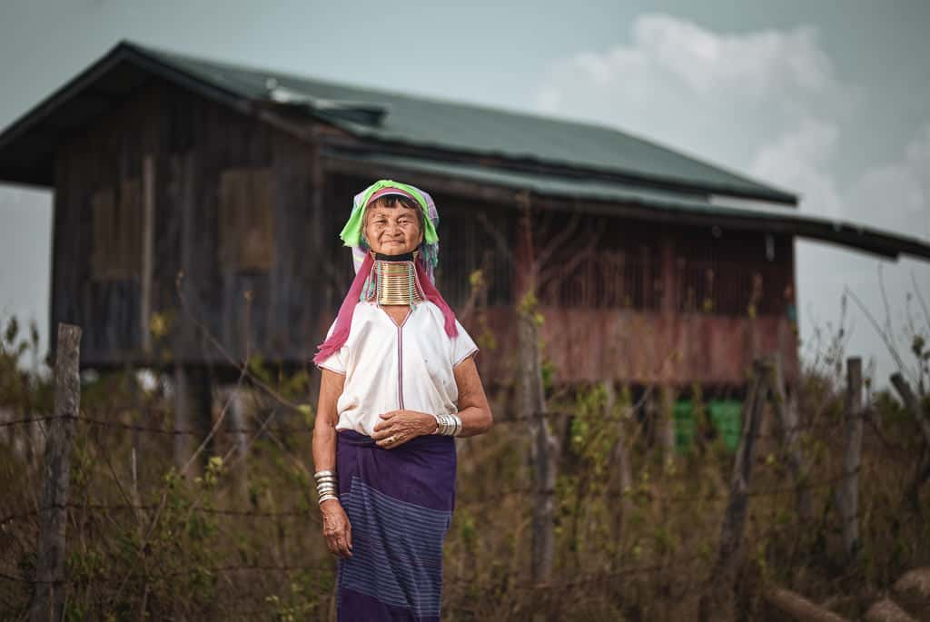 Kayan Lahwi woman in front of a traditional longhouse